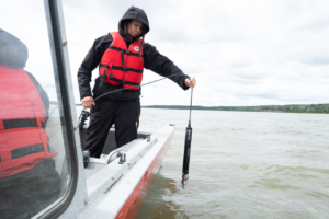 A member of the Dehcho K'ehodi Indigenous Guardians program tests water quality in the Northwest Territories.