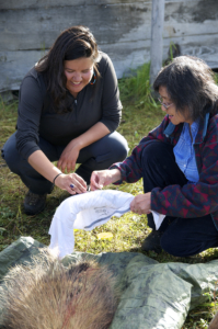 An Indigenous Guardian and elder work together at an Indigenous Guardians training camp at Dechenla Lodge, the Yukon.