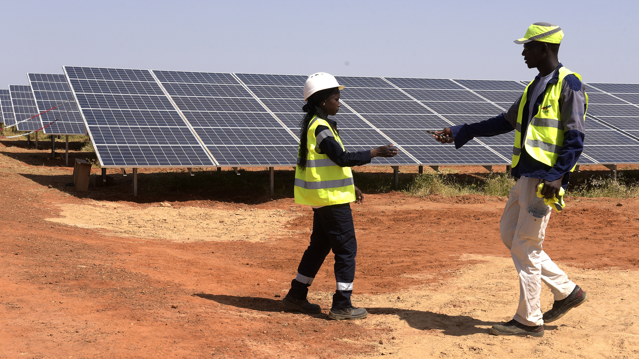Technicians walk through solar panels in Senegal