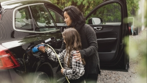 Mid adult woman teaching daughter to charge electric car at charging station