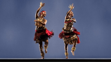 Two traditional Congolese dancers perform on stage.